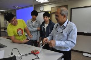 During a class experiment, Mr. Pakianathan demonstrates how to find acceleration with the speed of hands to juniors, Kelvin Lee, Isaac Kweon, and Kevin Lee.