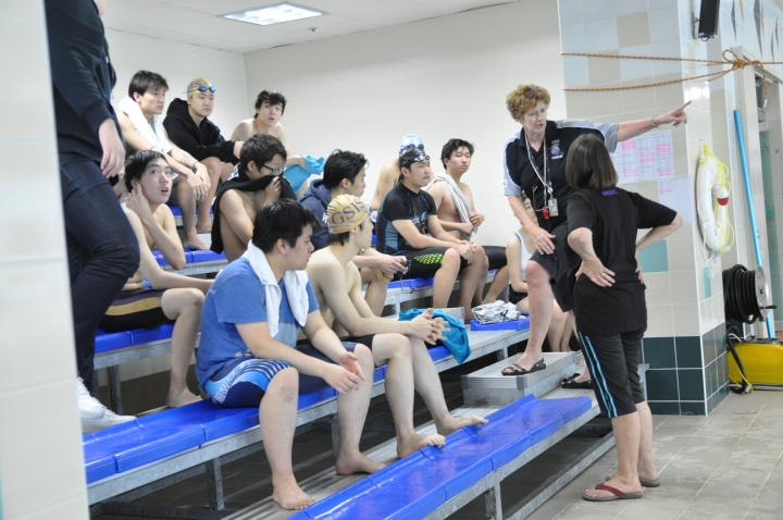 Mrs. Ivison rallies the Swim Team in a quick huddle.