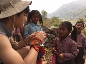 Paul Lee hands out stickers to the Nepali children at a village stop. The team brought balloons, beads, and other toys to give to the Nepali children as well.